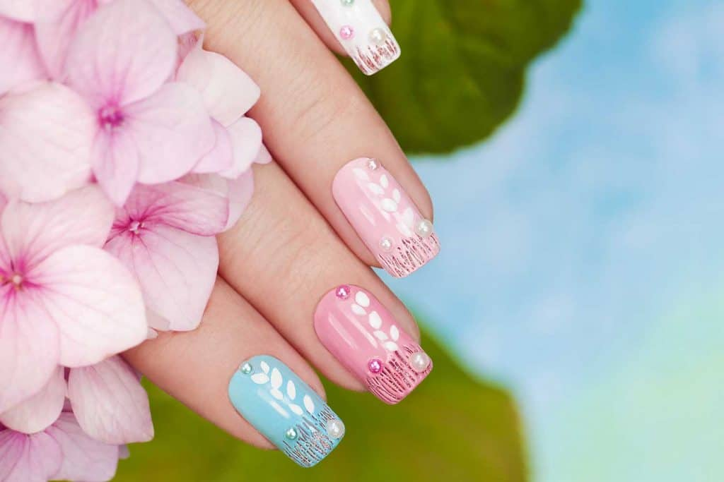 Pastel manicure with rhinestones and sequins on the background of Hydrangeas