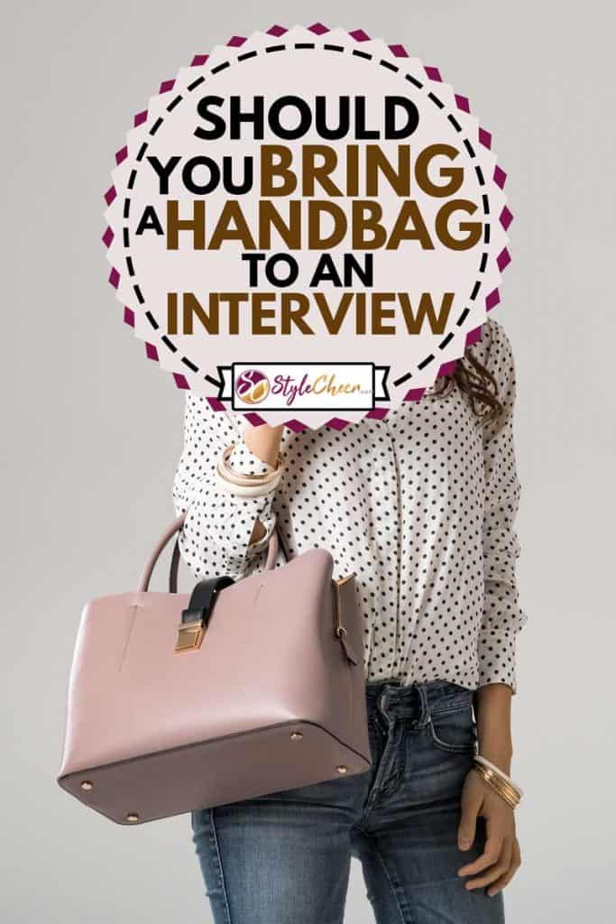 Young glamour woman wearing polka dot shirt and jeans posing with pink handbag during job interview, Should You Bring A Handbag To An Interview?