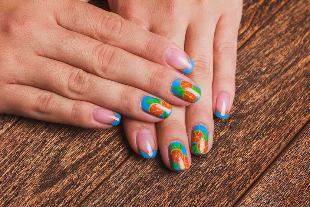 Summer french blue nail art with drawed orange fruit on wooden background