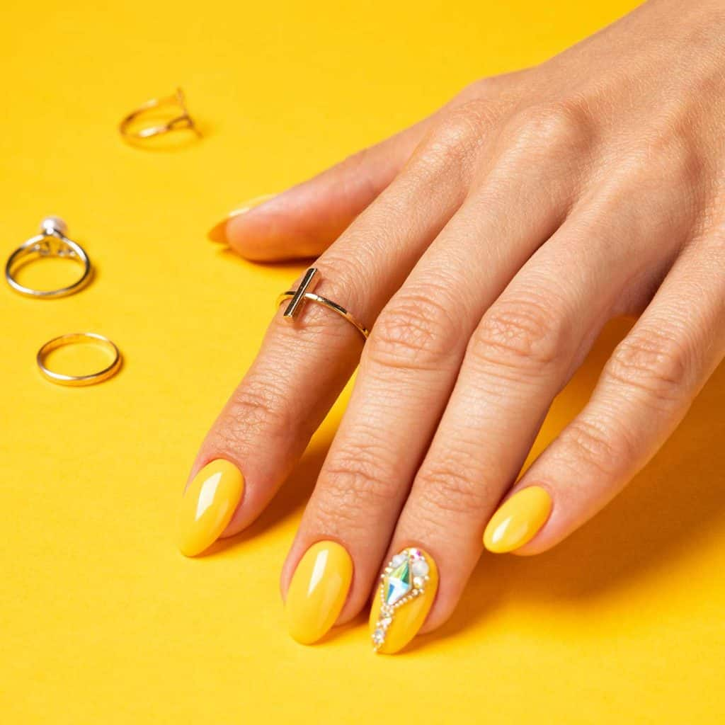 Summer yellow manicure with crystals and jewelry ring