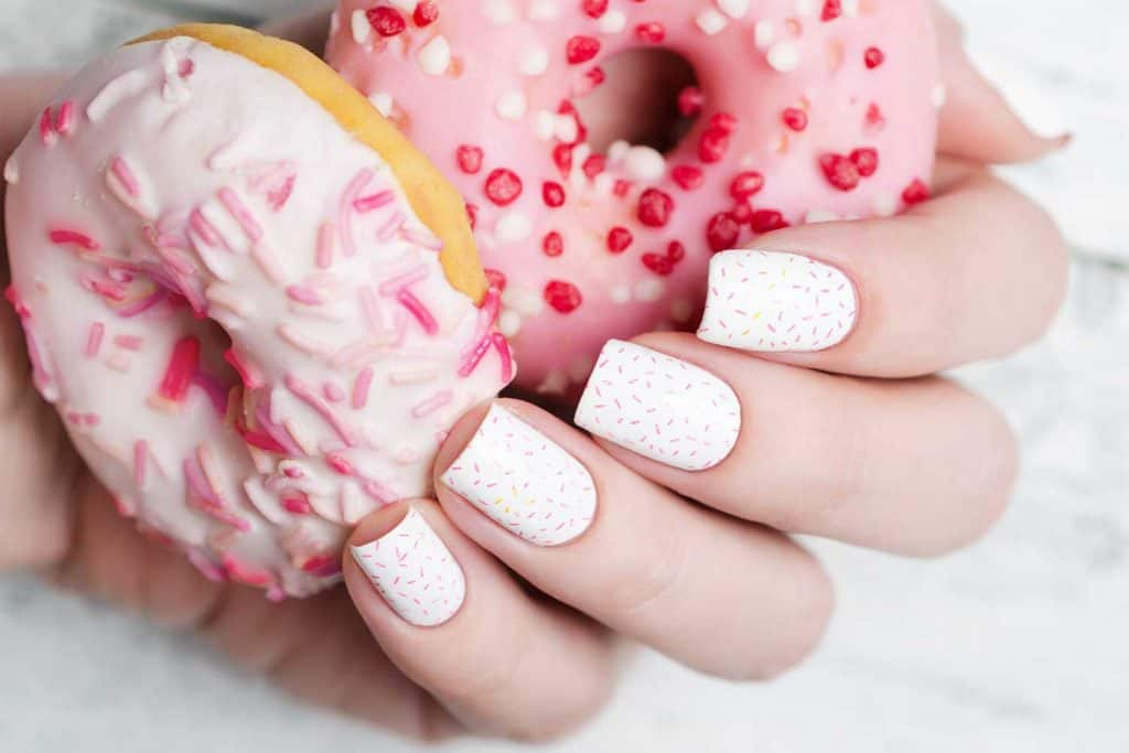 White manicure with pink sprinkle on donuts pattern