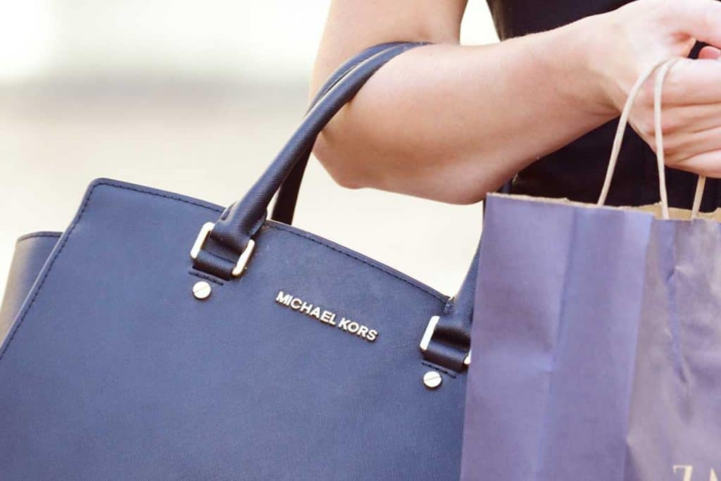 Woman shopping with blue Michael Kors handbag, Top 10 Handbag Brands Every Fashion Fan Should Know
