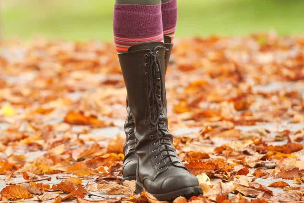 Woman walking in autumn wearing boots with socks, How To Wear Socks With Boots