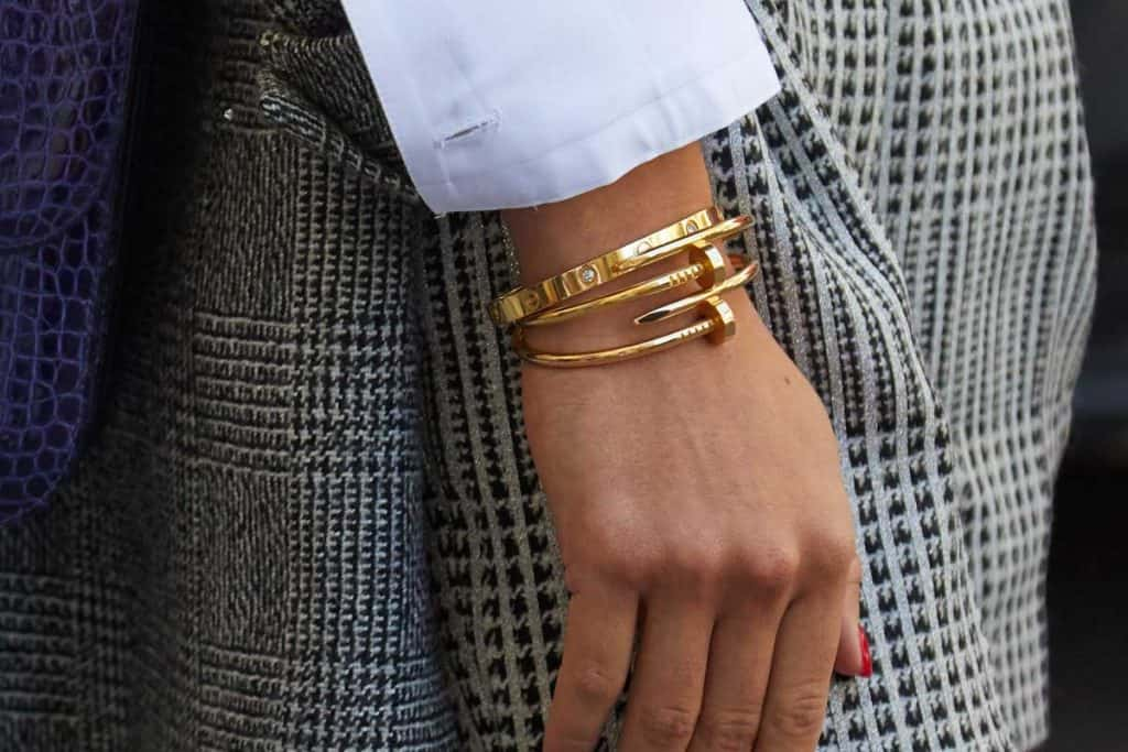 Woman with blue leather bag and golden Cartier bracelets, How Much Do Cartier Bracelets Cost?