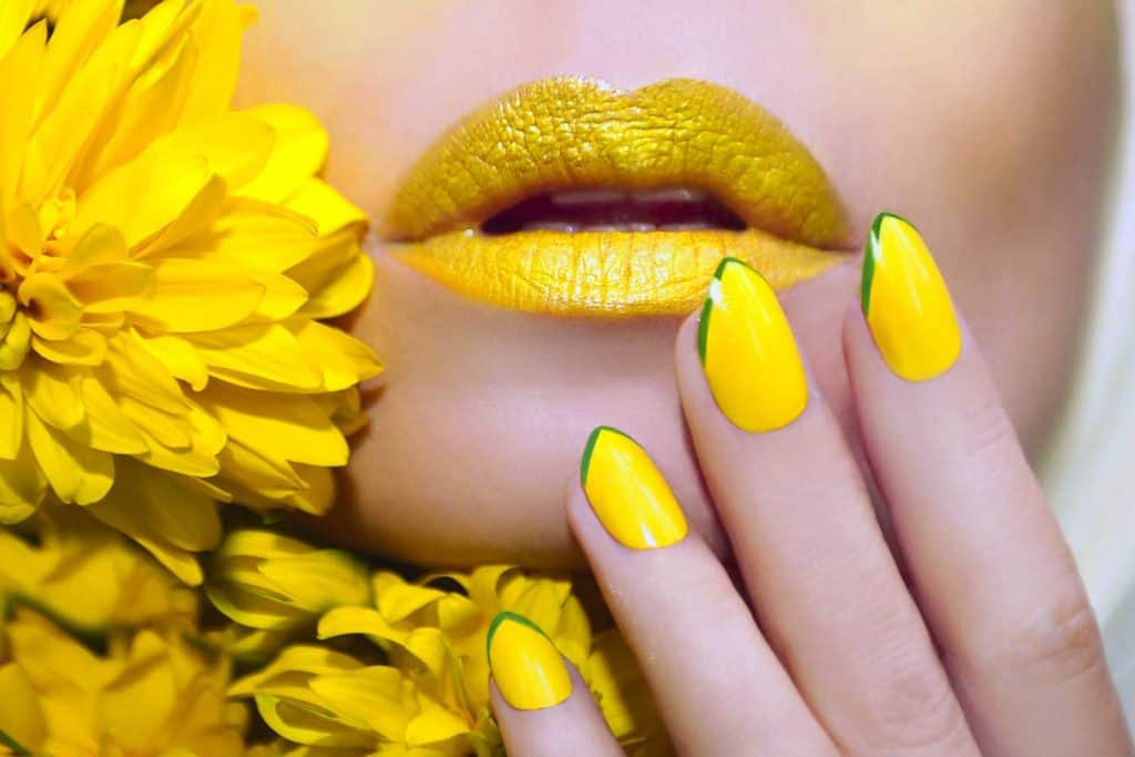 Yellow manicure and makeup on a woman with flowers