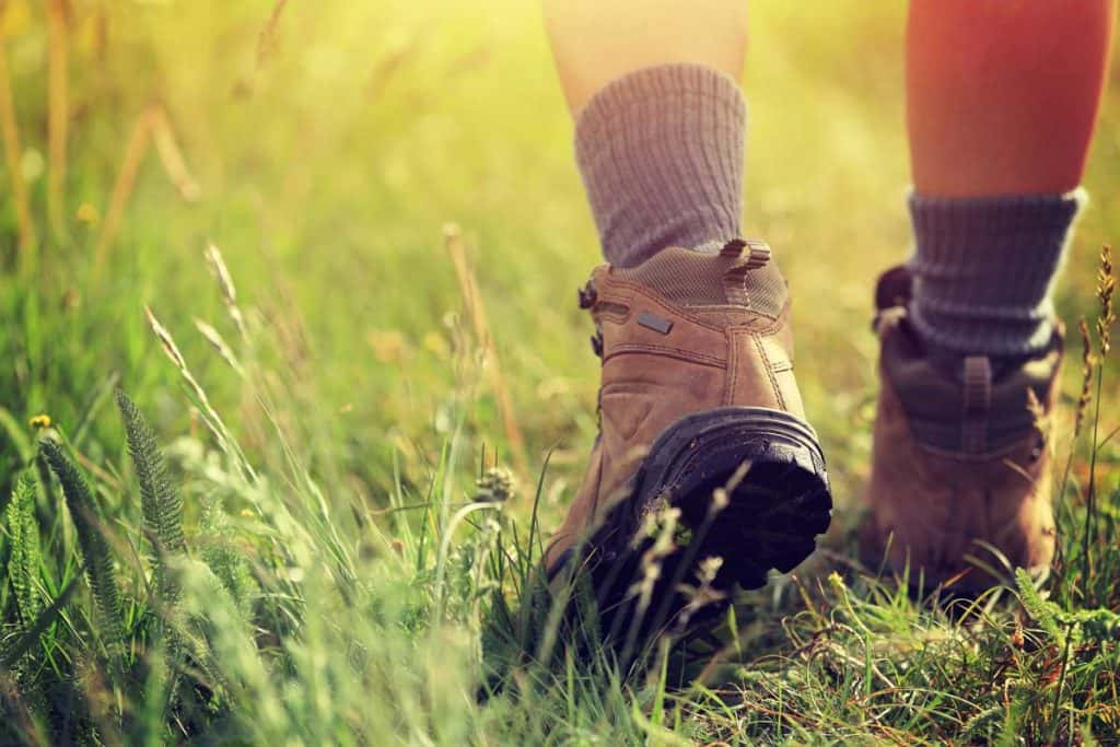 young woman hiker legs wearing boots while walking on trail in grassland, Do Boots Stretch As You Wear Them? [And how much]