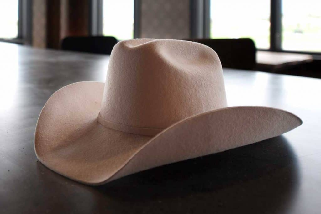 A cowboy hat lays on the bar in a an urban style saloon, How Much Does A Cowboy Hat Cost?
