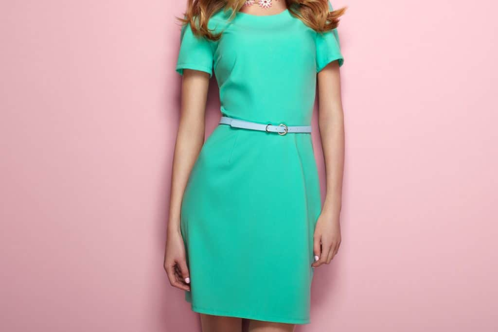 A woman wearing an elegant green dress with a light blue colored belt on, 23 Types of Belts Every Fashion Fan Should Know