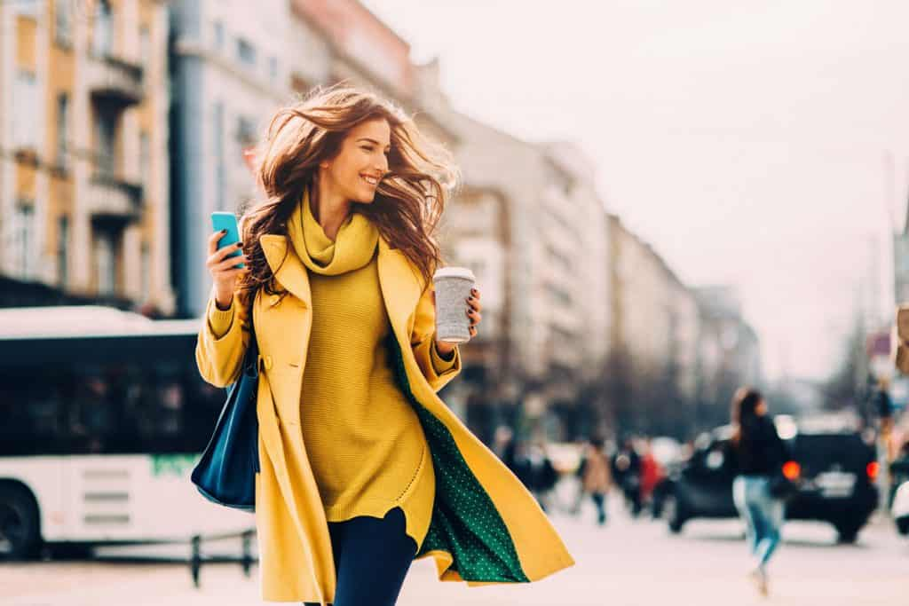 A woman wearing a mustard shirt and coat while texting and holding a cup of coffee, How to Wear Mustard Yellow? [37 Suggestions with Pictures]