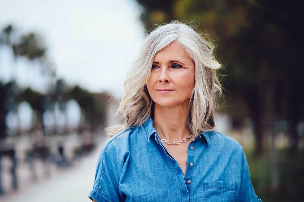 Beautiful fashionable mature woman with gray hair in the city street