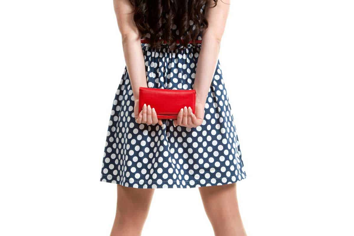 Beautiful girl in polka dots dress holding red purse, What Does A Red Purse Say About You?