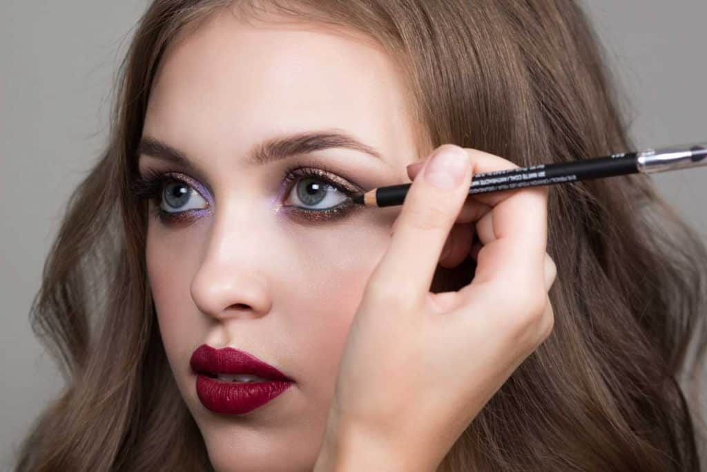Beautiful young woman and makeup artist's hand with a pencil for eyes, Does Bottom Eyeliner Make Eyes Smaller?