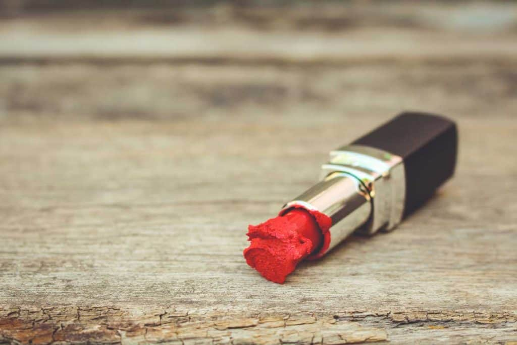Broken and old red lipstick on old wooden background.jpg