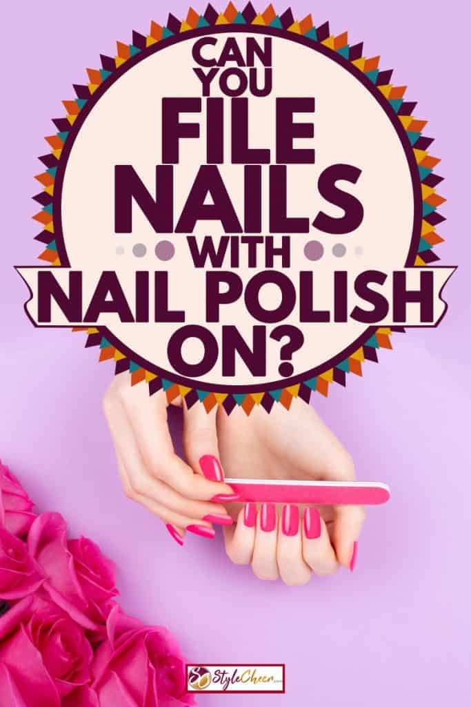 A woman filing her nails with a pink colored nail filer, Can You File Nails With Nail Polish On?