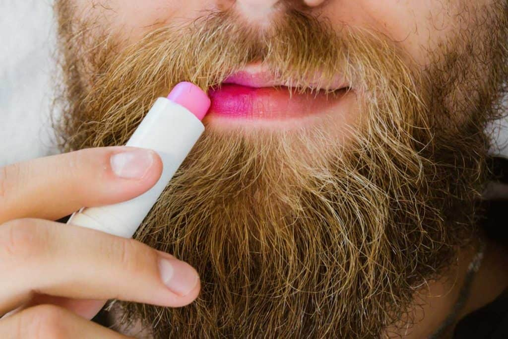 Close up of bearded man applying colorful pink lip balm on his lips, Should Guys Wear Lip Balm?