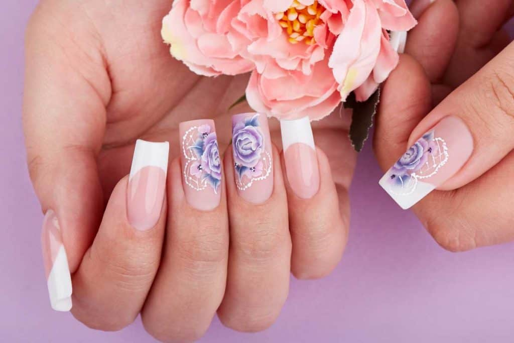 Hands with long artificial french manicured nails holding pink rose flower, How Often Should You Get a New Set of Acrylic Nails?