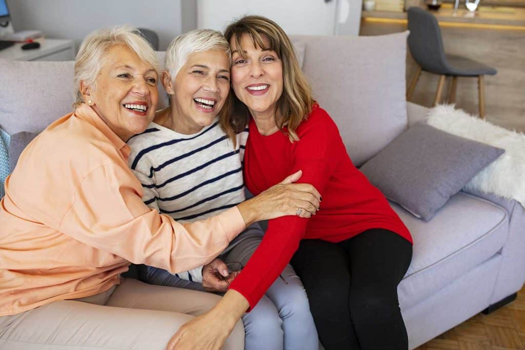 Happy senior women smiling and hugging at home