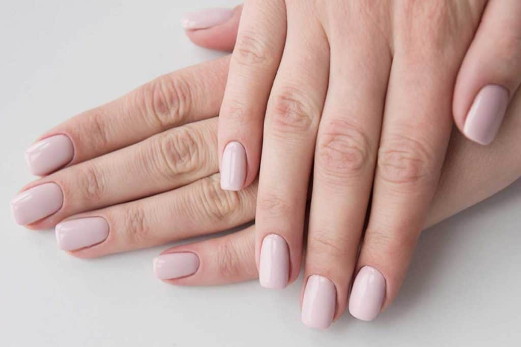 Nails manicured with beige dip powder, How Long Can You Keep Dip Nails On?