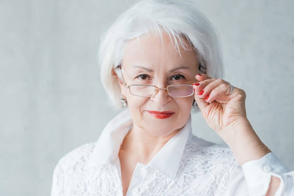 Confident elderly female looking intently over glasses