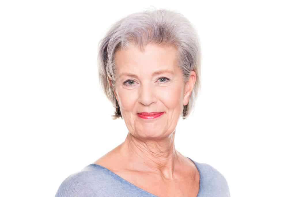 Smiling senior woman in front of a white background