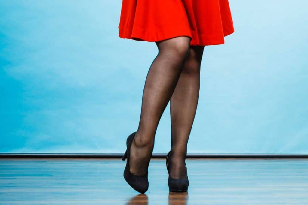 Woman wearing red dress, dark tights and black high heels, Should I Wear Tights with a Dress? [Here's How]