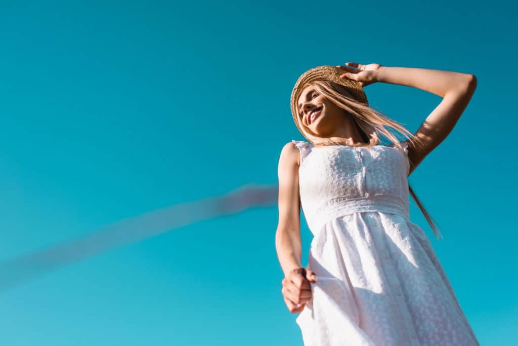 A woman posing happily while wearing a white dress on a blue sky, What Kind Of Dress To Wear As A Guest For A Beach Wedding?