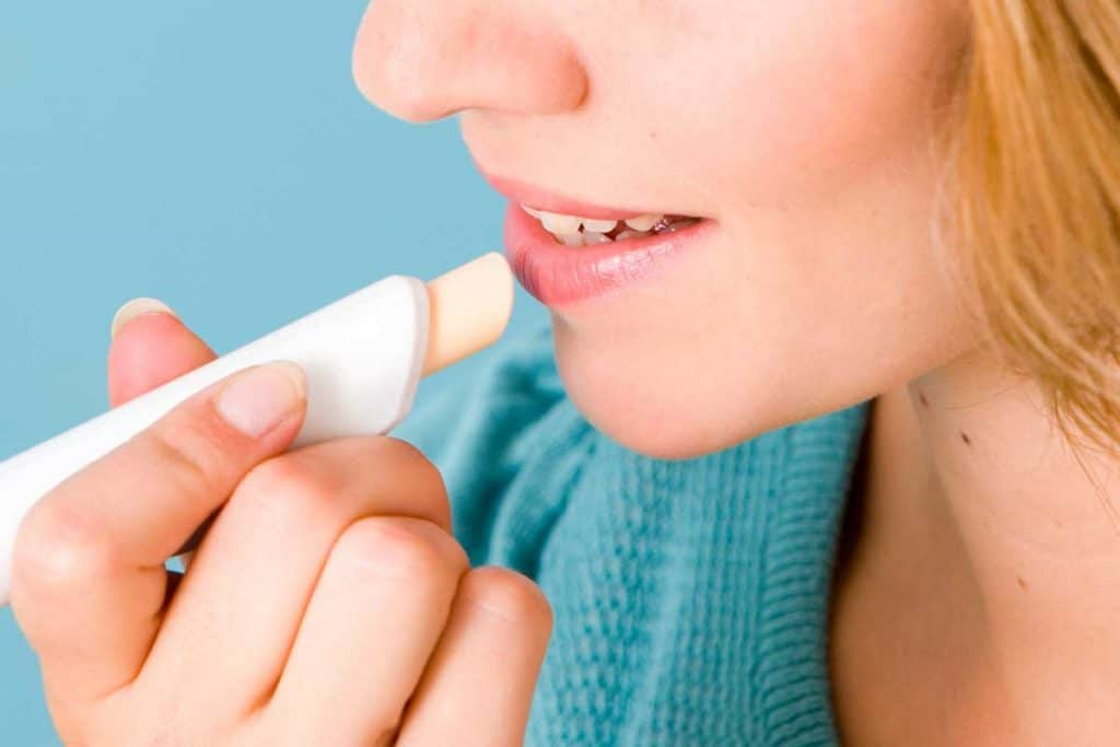 A woman putting chap protection lip balm, How Often Should You Apply Lip Balm?
