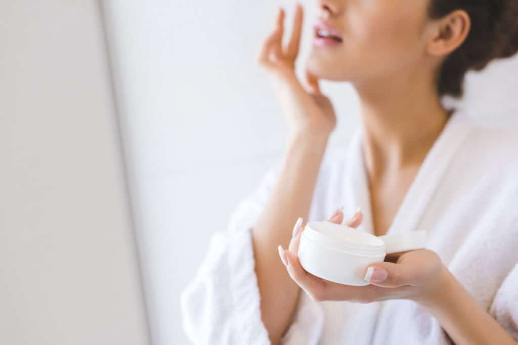 A woman putting on moisturizer on her face, Can You Use Day Moisturizer Overnight?,