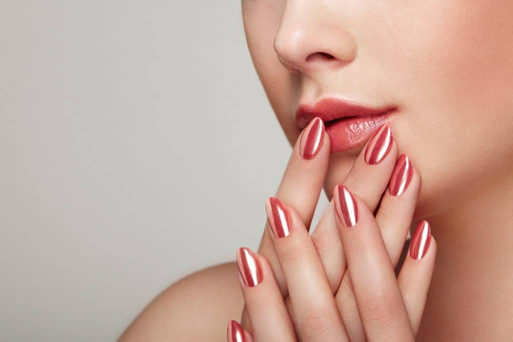 A woman showing her shinny newly polished nails and matching it with her lips, Should Lipstick Match Nail Polish?