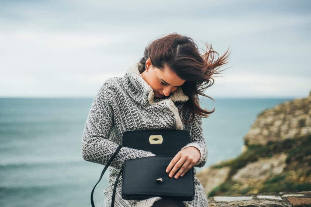 A woman wearing a sweater and holding her dark purse, Purse vs. Clutch vs. Handbag: What's the Difference?