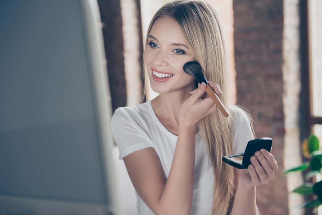 A young woman applying foundation to her face while staring on the mirror, Can You Use Lighter Foundation As Concealer?