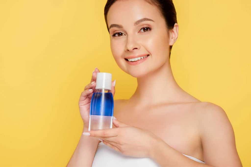 Beautiful woman holding micellar water in bottle, Can You Use Micellar Water Instead Of Cleanser?