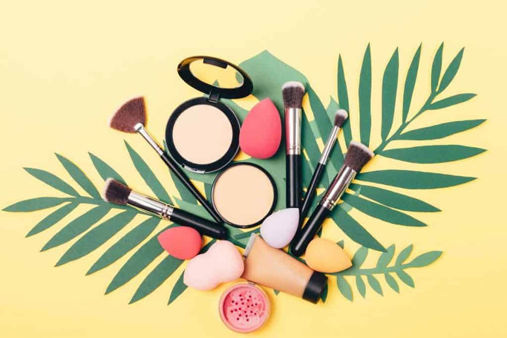 Beauty makeup products and tools including blending brush on palm leaves on yellow background, What Is the Best Blending Brush? [3 Recommendations!]