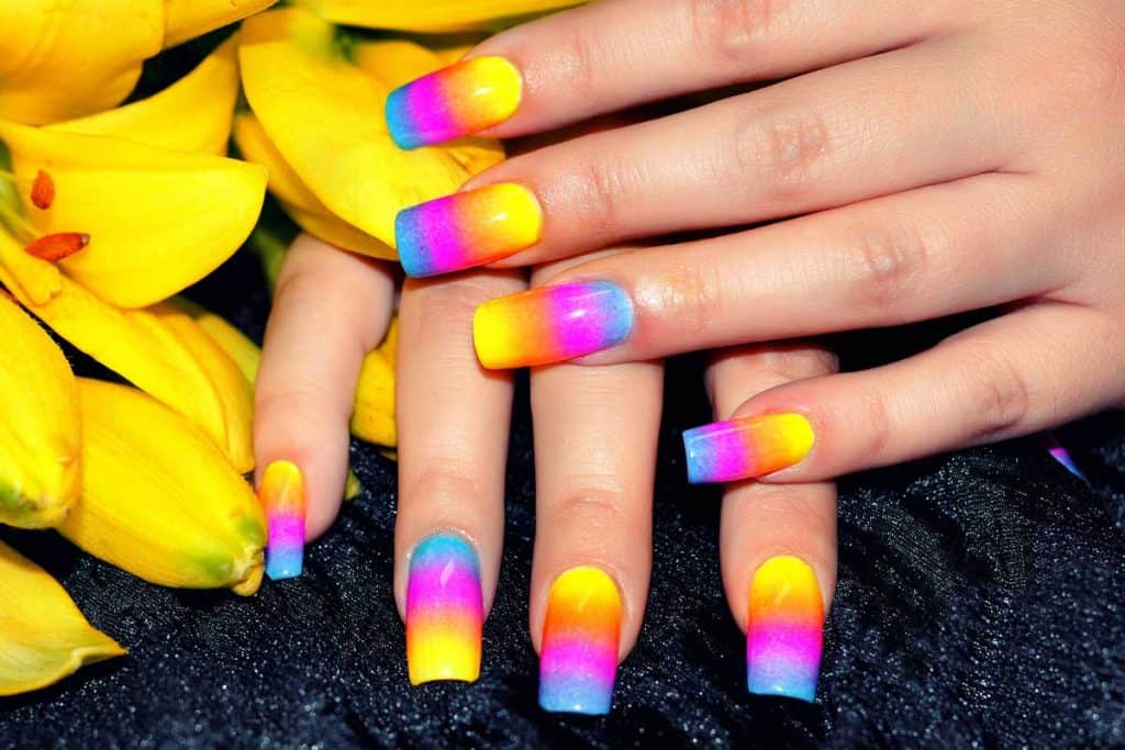 Female hands with colorful nail design holding beautiful yellow flower, 22 Bright Summer Nail Color Ideas