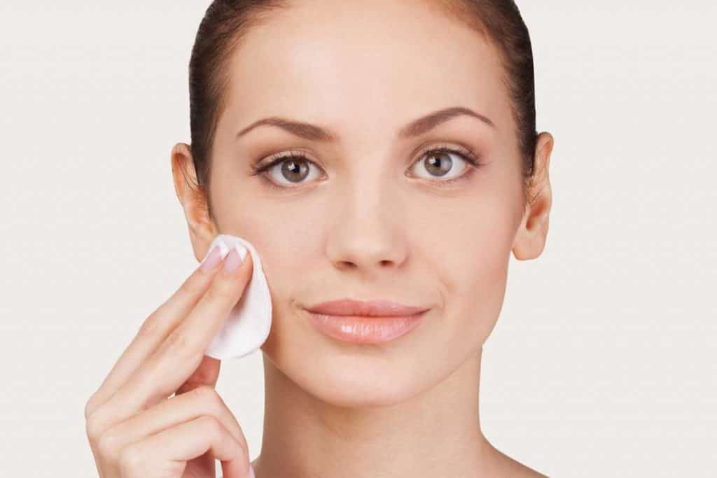 Portrait of a cheerful woman smiling while applying toner on her face, 5 Great Alternatives To Cotton Pads For Toner