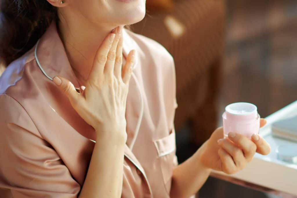 Woman in pajamas with pink cosmetic jar applying neck cream, When Should You Start Using Neck Cream?