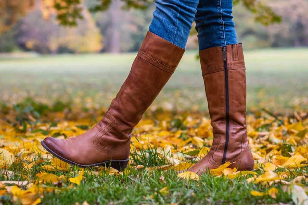 Woman wearing brown leather boots and walking in fallen leaves, Is Your Boot Size the Same as Your Shoe Size?