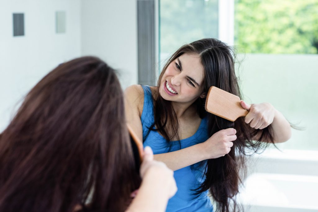 A brunette combing her hair after taking a shower in her modern bathroom, How To Stop Frizzy Hair After Washing?