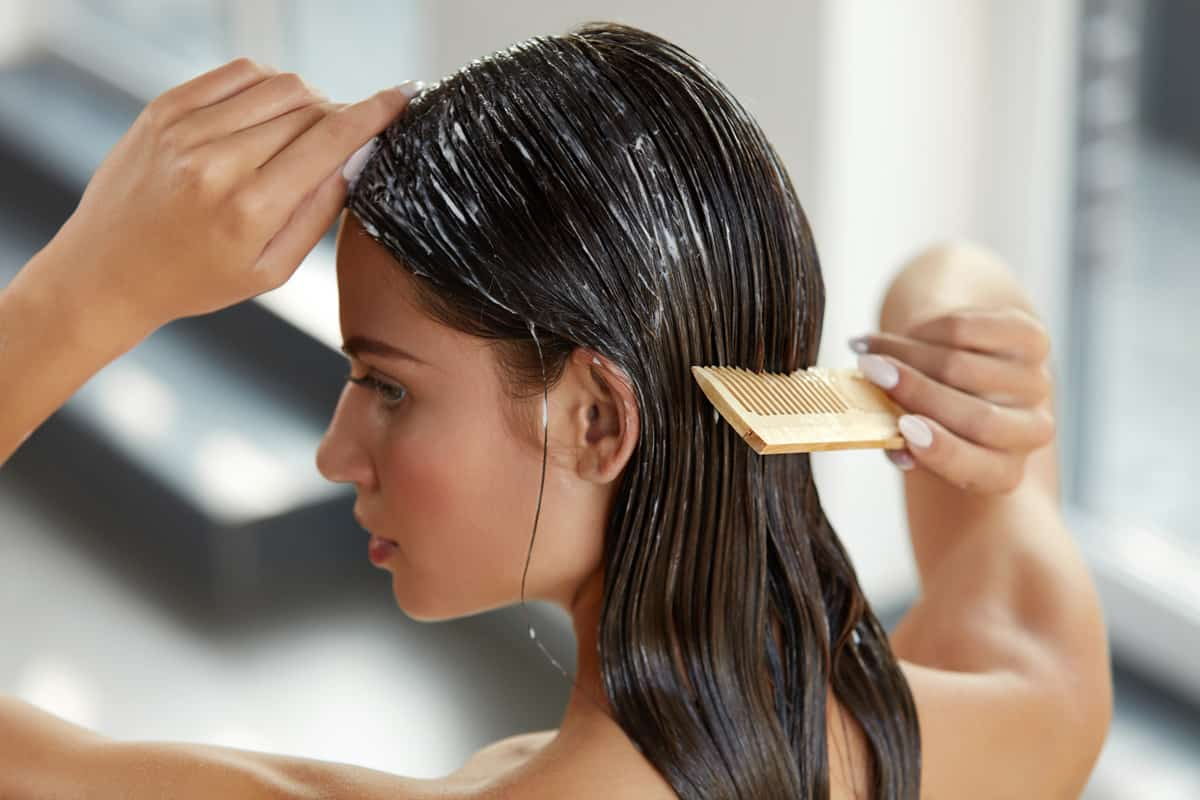 A woman putting on conditioner hair on her hair and combing it to spread it evenly throughout her hair, Can I Condition My Hair Every Day?