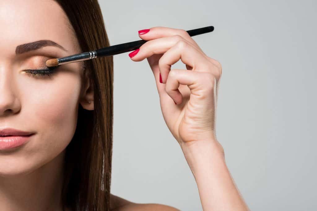 A woman putting on eyeshadow using a beauty brush