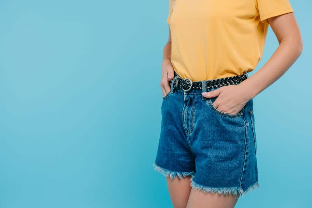 A woman wearing a yellow top and denim shorts with a belt buckle, 19 Types of Belt Buckles Every Fashion Fan Should Know