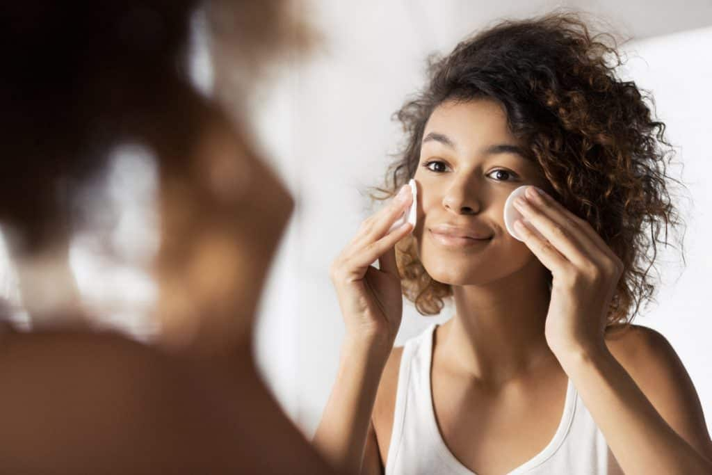 A young beautiful woman removing makeup on her face