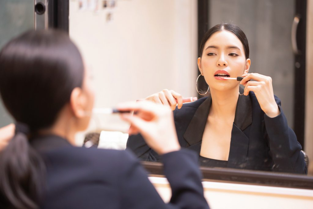 An Asian business agent wearing tux formally while putting on lipstick