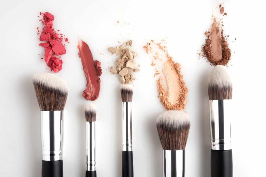 Different kinds of beauty products and brushes placed on a white background