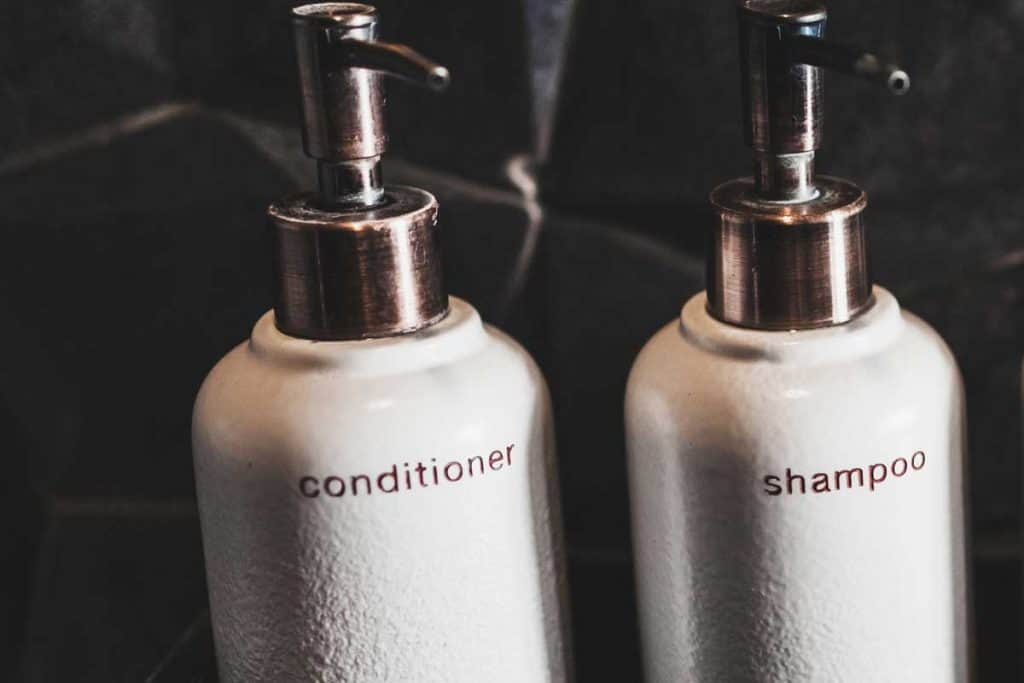 White metal bottles of shampoo and conditioner on wooden shelf, Is It Good To Mix Shampoo With Conditioner?