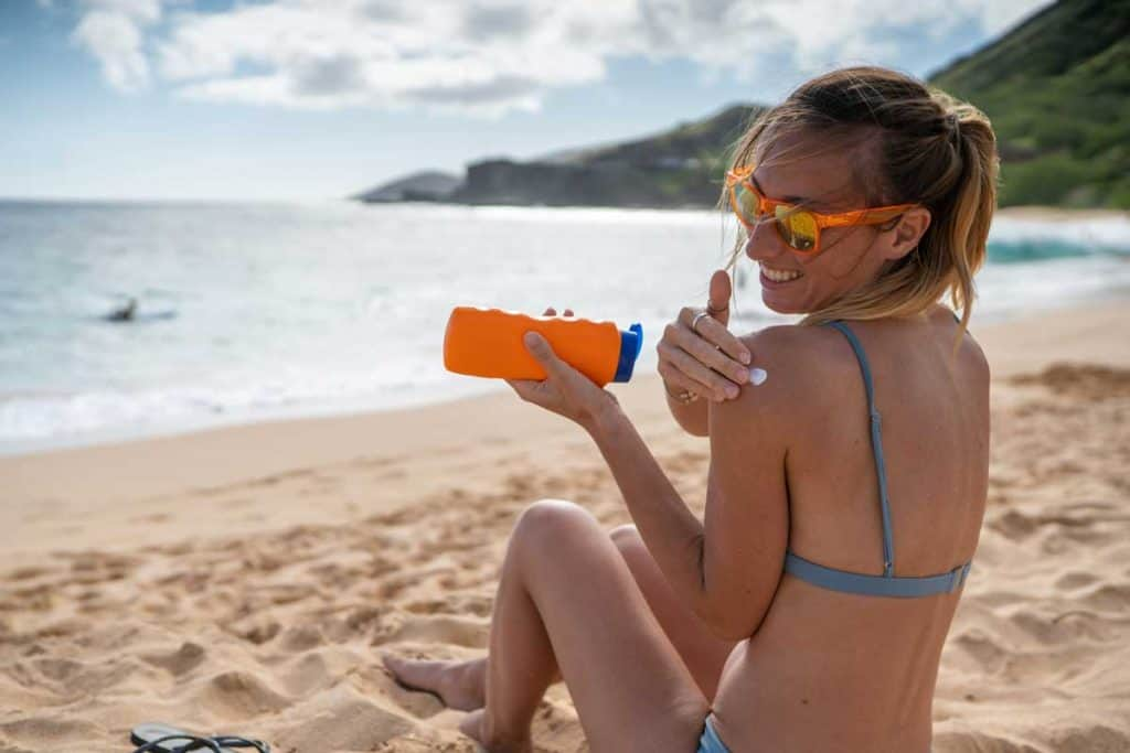 Young woman on beach applying sunscreen on her face, protection on skin and sunbathing tan concept, Do You Use Sunscreen Before Or After Moisturizer?