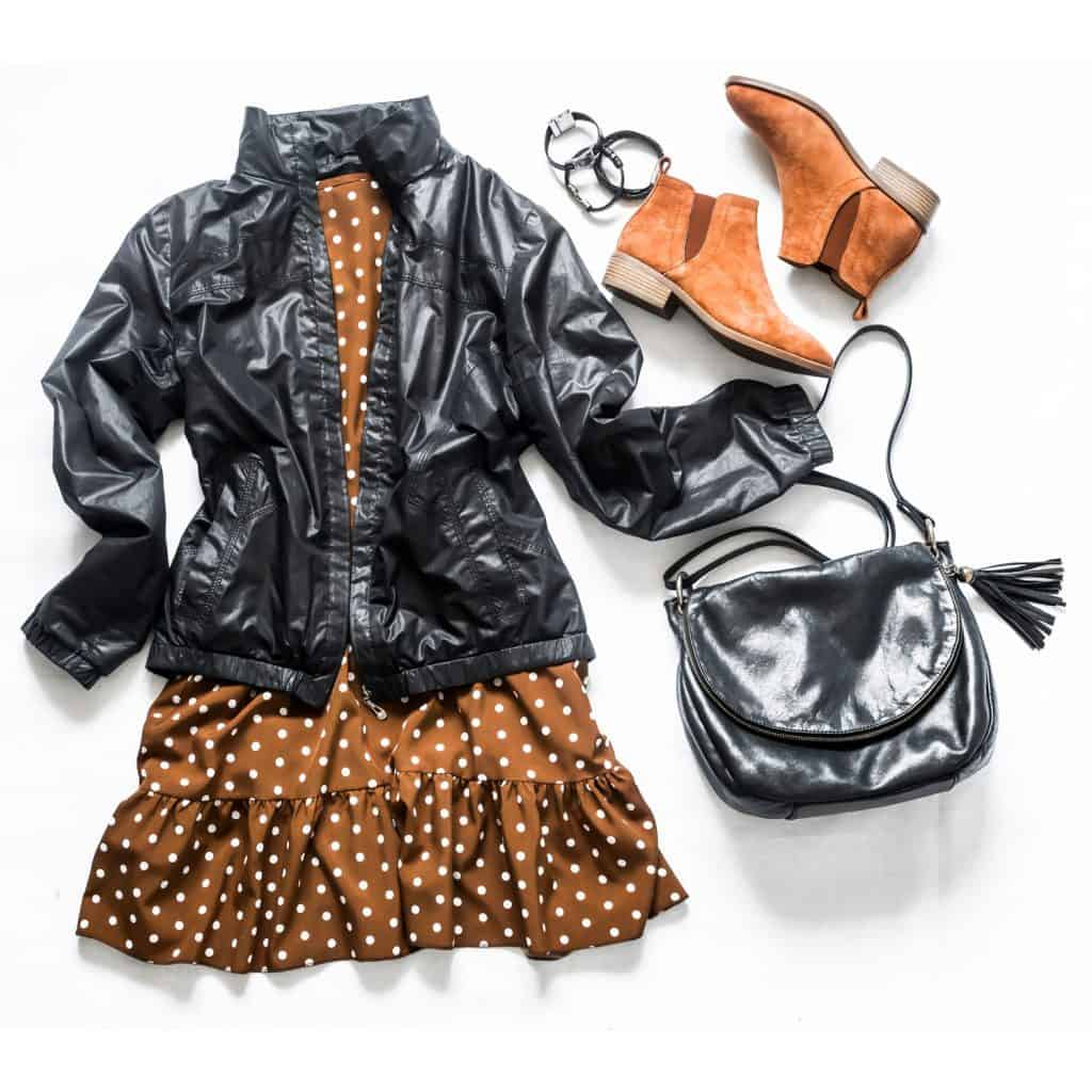 A black sling bag, windbreaker jacket, brown polka dot dress, leather bracelets, and a pair of Chelsea brown boots
