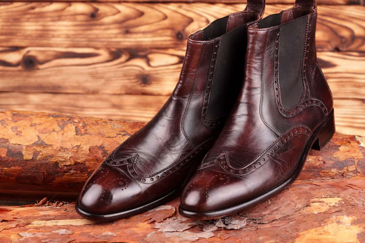 Gorgeous brown Chelsea boots placed on a wooden table, Are Chelsea Boots Waterproof? [And Are They Good For Snow]