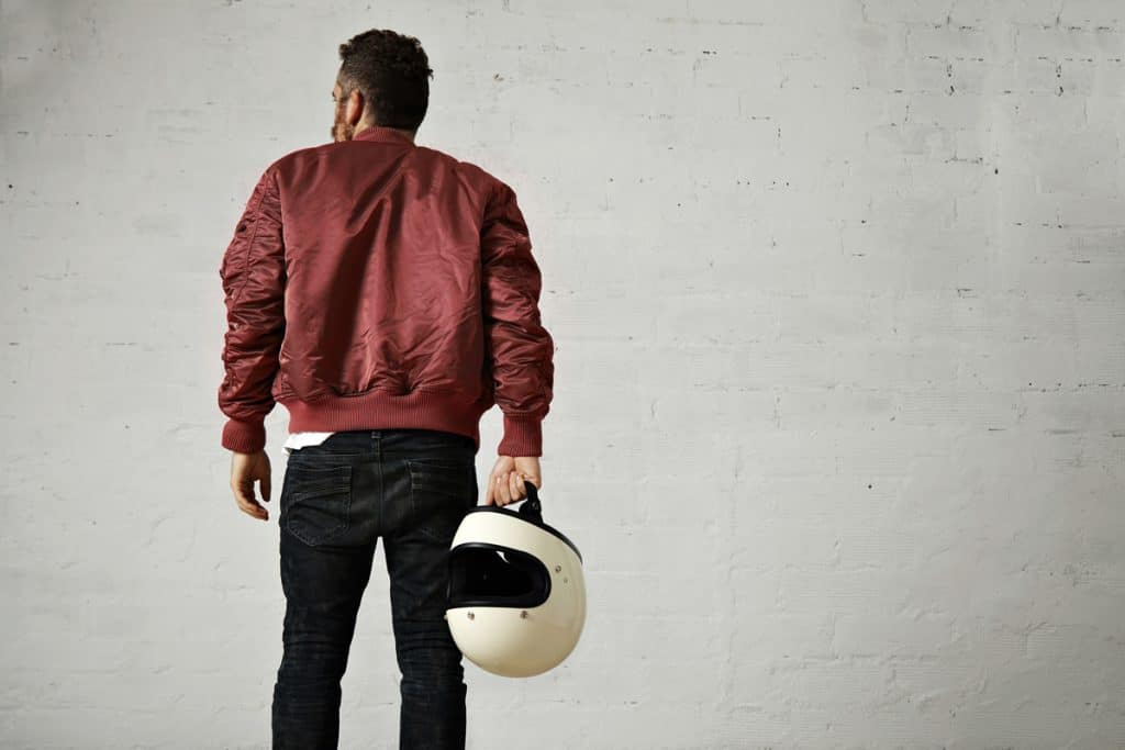 Man wearing a bomber jacket and holding a helmet while staring at a gray wall, Are Bomber Jackets Warm Enough For Winter?