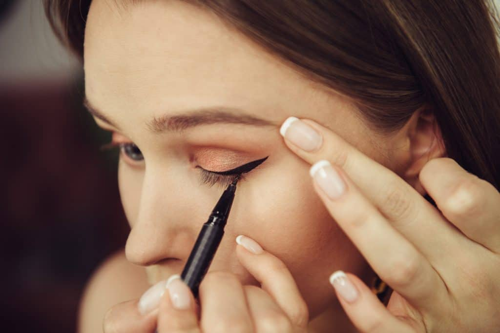 A woman putting on eyeliner on her eyelid before applying eyeshadow